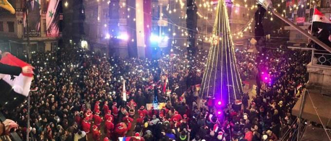 Στο ελεύθερο Χαλέπι γιορτάζουν τα Χριστούγεννα με σημαίες της Συρίας και της Ρωσίας .